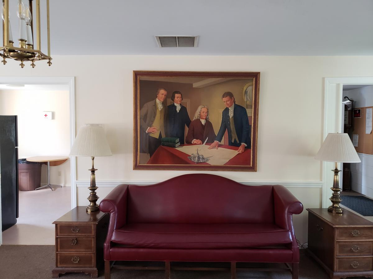 couch with a painting of founding fathers above