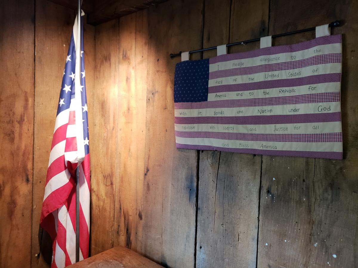 an american flag quilt on a wall next to an american flag