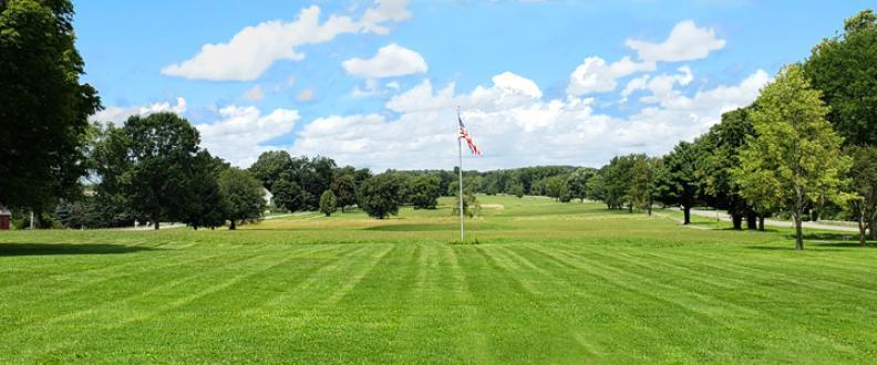 An American flag hangs against the blue sky above the freshly mowed Lebanon Green